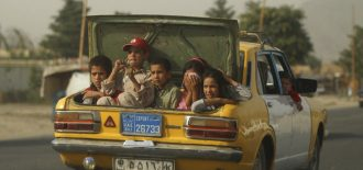 Afghan children sit on the back of a taxi as they drive through the street of Kabul, Afghanistan, Wednesday, Aug. 6, 2008. (AP Photo/Ahmad Masoud)